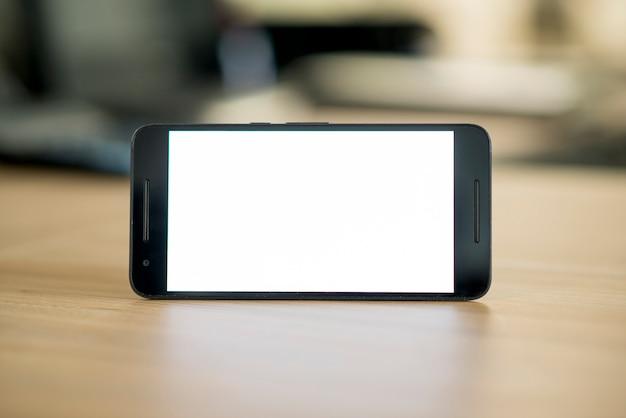 Smartphone met leeg wit scherm over houten bureau Gratis Foto
