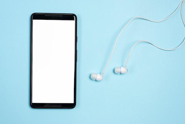 Smartphone met oortelefoons op blauwe achtergrond Gratis Foto