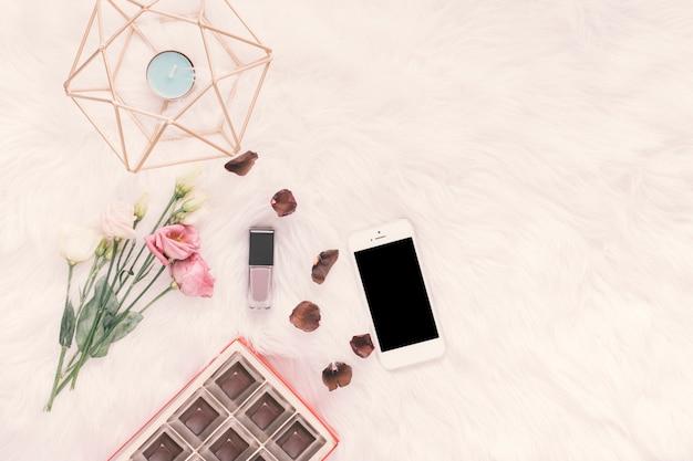 Smartphone met rozen en chocoladesnoepjes op deken Gratis Foto