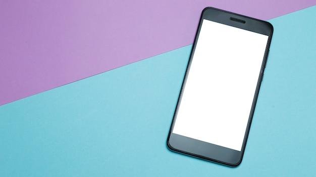 Smartphone met wit scherm op gekleurd papier minimalisme achtergrond. Premium Foto