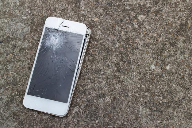 Smartphone mobiel valt op de cementen vloer met touchscreen bro Premium Foto