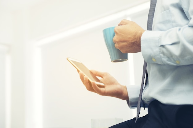 Smartphone ter beschikking van zakenman tijdens koffie-onderbreking die e-mail controleert Premium Foto