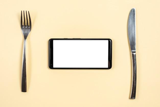 Smartphone tussen de roestvrij staalvork en butterknife op beige achtergrond Gratis Foto