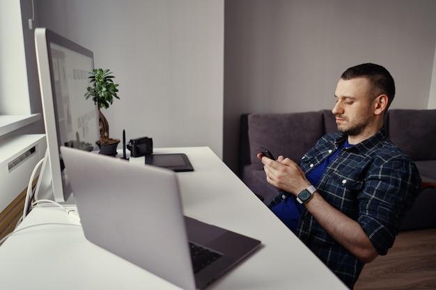 Smartphone van de jonge mensenholding in handen terwijl het maken van een pauze in huisbureau Gratis Foto