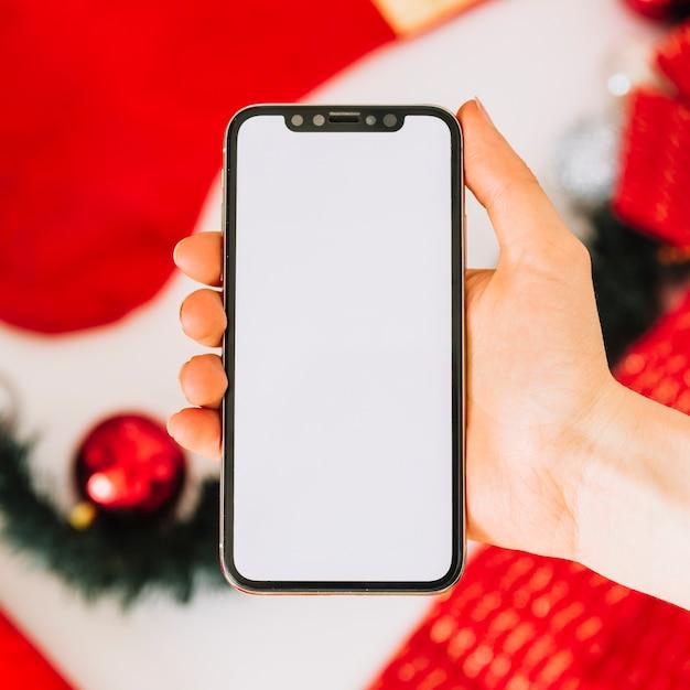 Smartphone van de vrouwenholding boven lijst met kerstboomdecoratie Gratis Foto