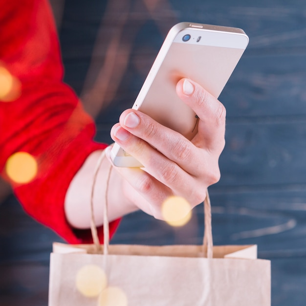 Smartphone van de vrouwenholding en giftzak Gratis Foto