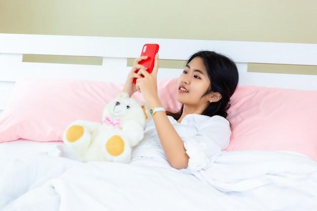 Smartphone van het tiener de vrouwelijke gebruik op het bed Gratis Foto