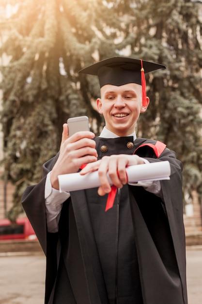 Smiley afgestudeerd jongen met mobiel Gratis Foto