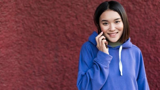 Smiley aziatische vrouw praten over de telefoon Gratis Foto