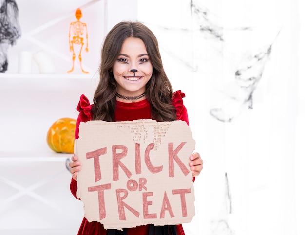 Smiley jong meisje bedrijf trick or treat teken Gratis Foto