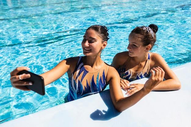 Smiley jong meisje dat een selfie neemt bij het zwembad Gratis Foto