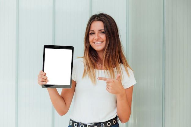 Smiley jong meisje dat op tablet richt Gratis Foto
