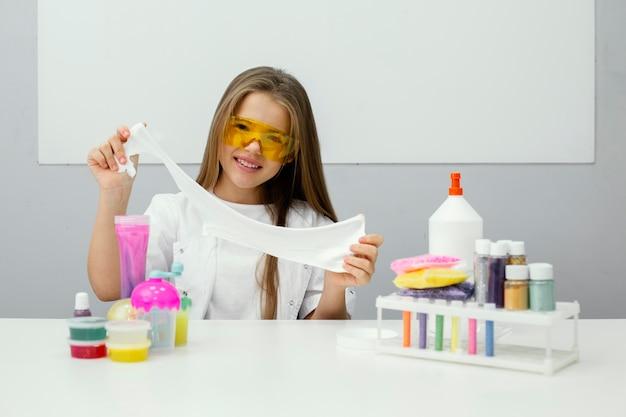 Smiley jong meisje wetenschapper experimenteren met slijm Premium Foto