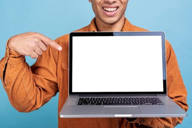 Smiley jonge man toont een laptop Gratis Foto