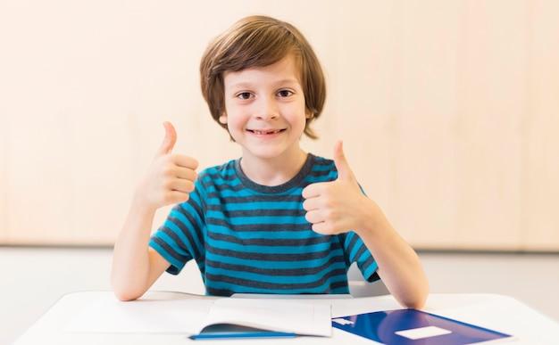 Smiley jongen doet de duimen omhoog teken Gratis Foto