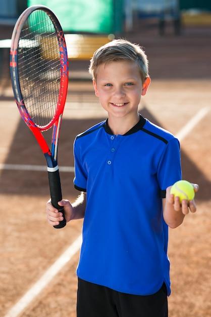 Smiley jongen houdt een tennisracket en een bal Gratis Foto