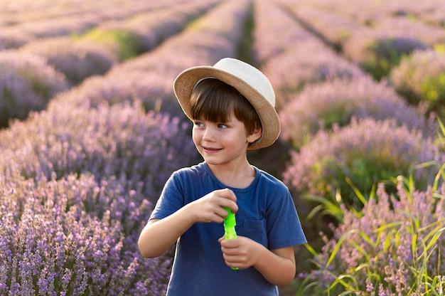 Smiley jongetje in bloem veld Gratis Foto