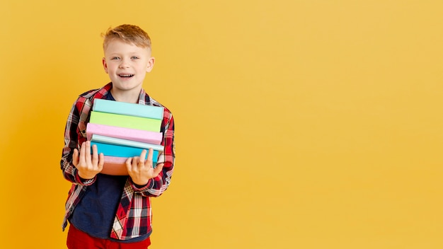 Smiley jongetje met stapel boeken Gratis Foto