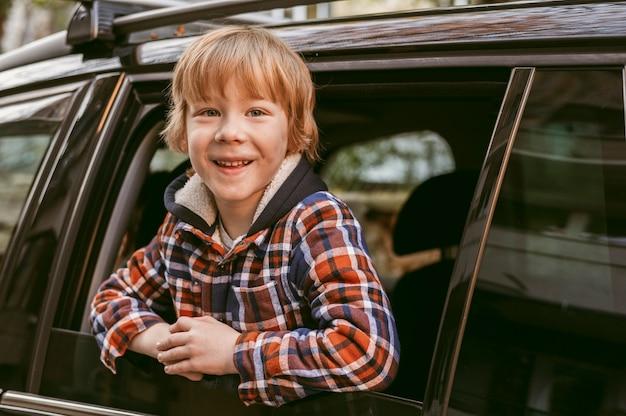 Smiley-kind in de auto tijdens een roadtrip Gratis Foto