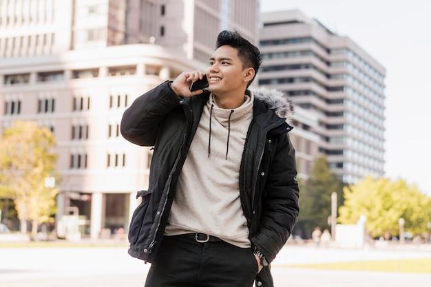 Smiley man praten aan de telefoon buitenshuis Premium Foto