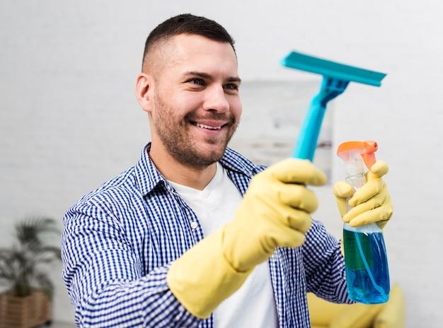 Smiley man schoonmaken met venster veegt af Gratis Foto