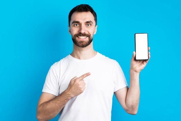 Smiley man wijzend op smartphone Gratis Foto