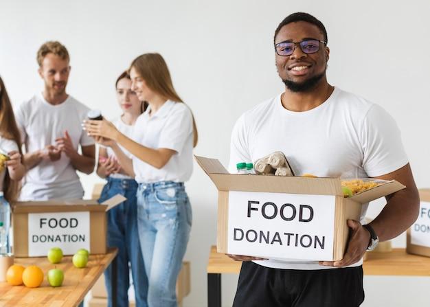 Smiley mannelijke vrijwilliger die voedselschenkingen houdt Gratis Foto