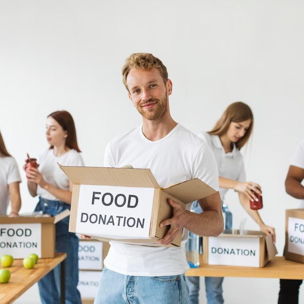 Smiley mannelijke vrijwilliger met voedseldonaties Gratis Foto