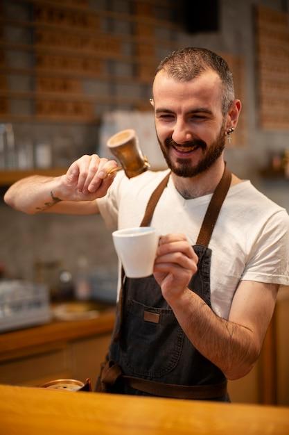 Smiley mannelijke werknemer van coffeeshop Gratis Foto