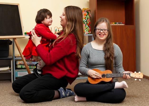 Smiley meisje met down syndroom en vrouw met kind Premium Foto