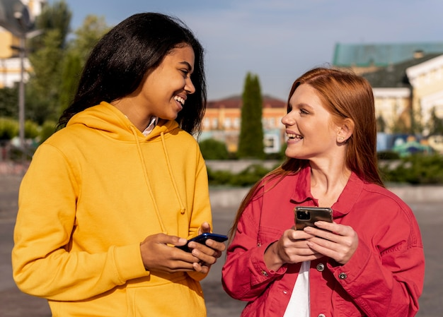 Smiley-meisjes die hun telefoons controleren Gratis Foto