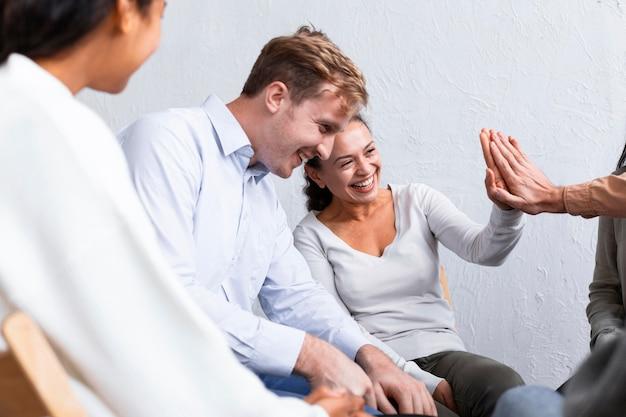Smiley-mensen bij een groepstherapie-sessie geven elkaar een high-five Gratis Foto