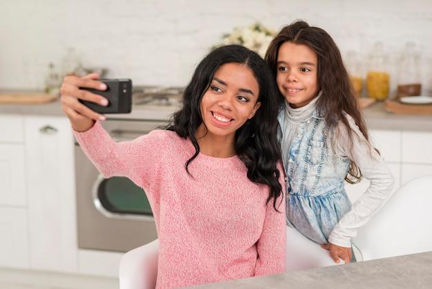 Smiley moeder en dochter fotograferen Gratis Foto