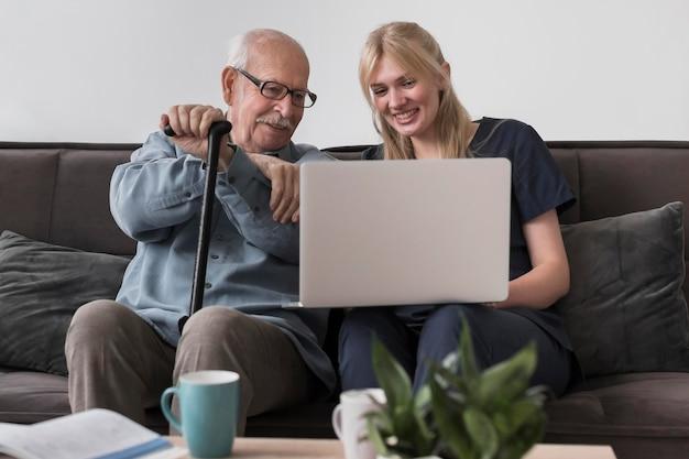 Smiley oude man en verpleegster met behulp van laptop Gratis Foto