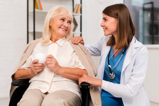 Smiley oude vrouw praten met verzorger Gratis Foto