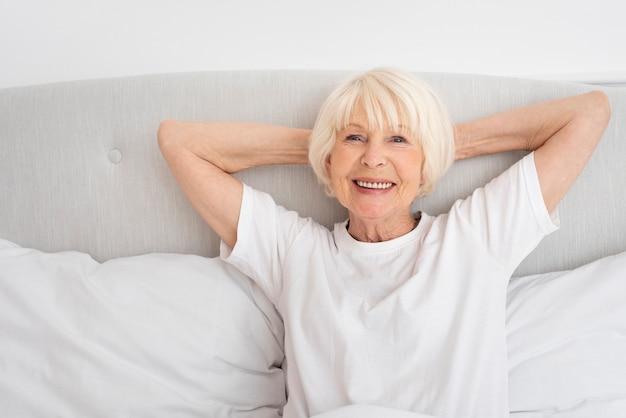 Smiley oude vrouw zitten in de slaapkamer Gratis Foto
