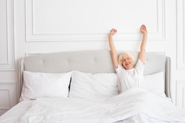 Smiley oudere vrouw die in de slaapkamer legt Gratis Foto