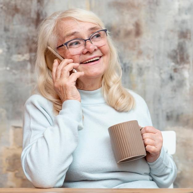 Smiley oudere vrouw die van huis werkt Gratis Foto