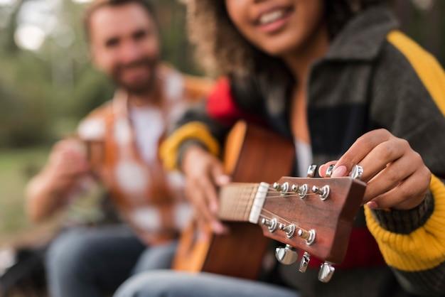 Smiley paar gitaarspelen buitenshuis tijdens het kamperen Gratis Foto