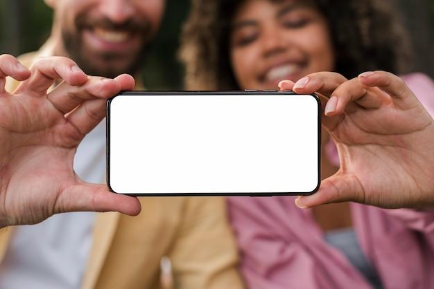 Smiley paar smartphone houden tijdens het kamperen buiten Gratis Foto