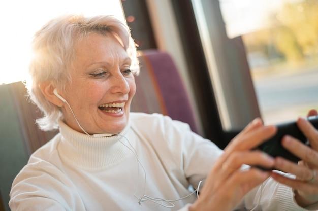 Smiley senior vrouw luisteren muziek Gratis Foto