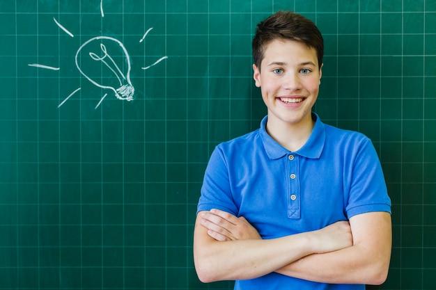 Smiley student voor het schoolbord Gratis Foto