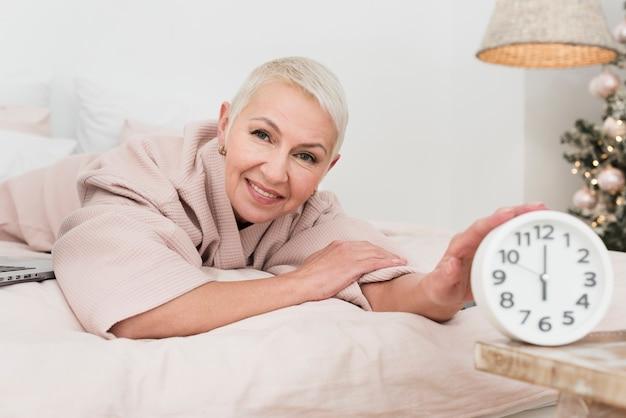 Smiley volwassen vrouw in badjas poseren in bed met klok Gratis Foto