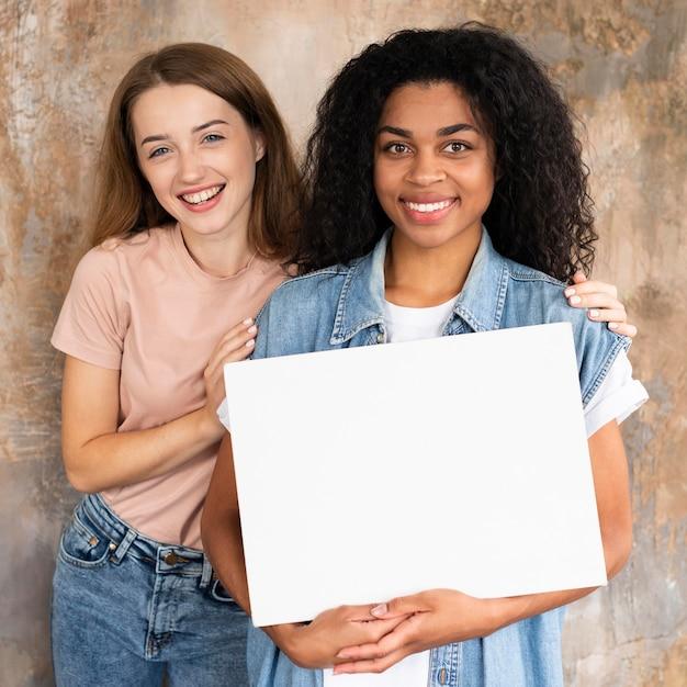 Smiley vriendinnen die samen poseren terwijl ze leeg bordje vasthoudt Gratis Foto