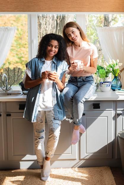 Smiley vriendinnen poseren in de keuken terwijl ze mokken vast houden Gratis Foto