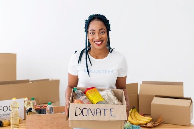 Smiley-vrijwilliger met een doos met donaties Gratis Foto