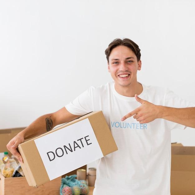 Smiley-vrijwilliger wijst naar een donatiebox Gratis Foto