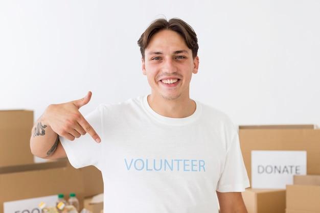 Smiley-vrijwilliger wijst naar zijn t-shirt Gratis Foto