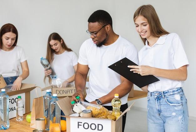 Smiley-vrijwilligers die doos met voedsel voorbereiden voor donatie Gratis Foto