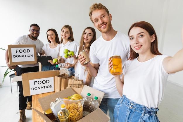 Smiley-vrijwilligers nemen samen selfie terwijl ze eten klaarmaken voor donatie Gratis Foto